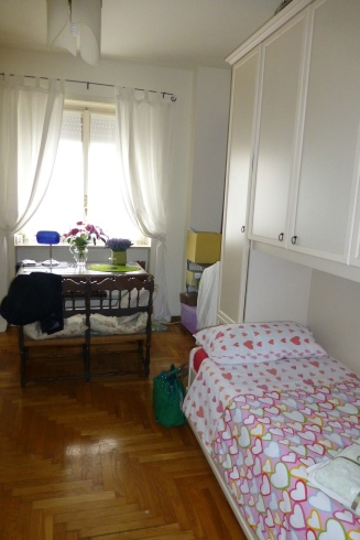 My home away from home - a comfy bed and a desk facing the window with fresh flowers.