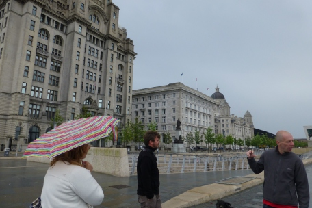 Tour guide and the Three Graces at the Liverpool waterfront
